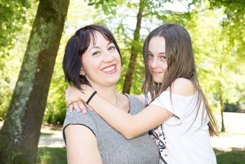 Modern och hennes nätta dottertonåring som ler och poserar i trädgård, parkerar arkivbild