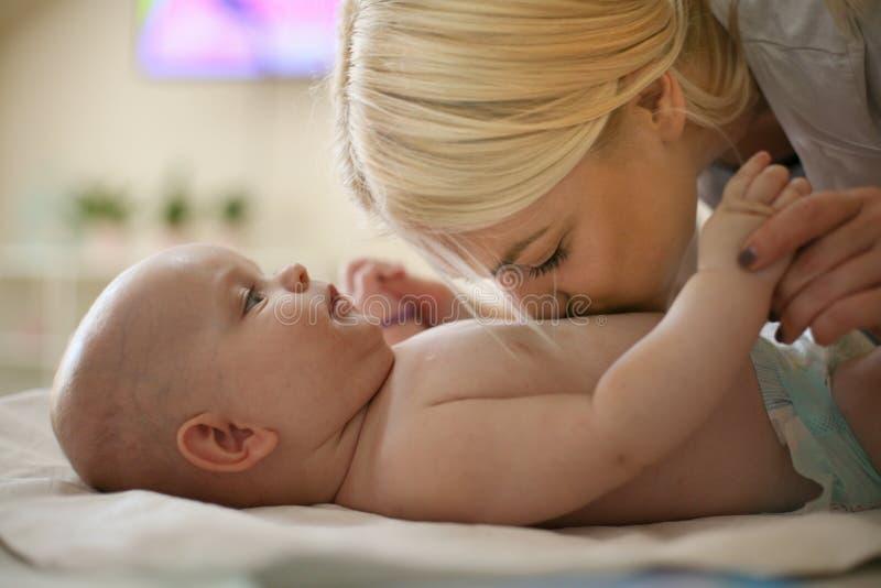 Modern och hennes små behandla som ett barn att tycka om hemma på säng royaltyfria bilder