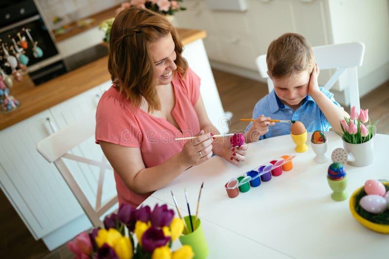 Modern och hennes son som har gyckel, dekorerar ägg arkivbilder