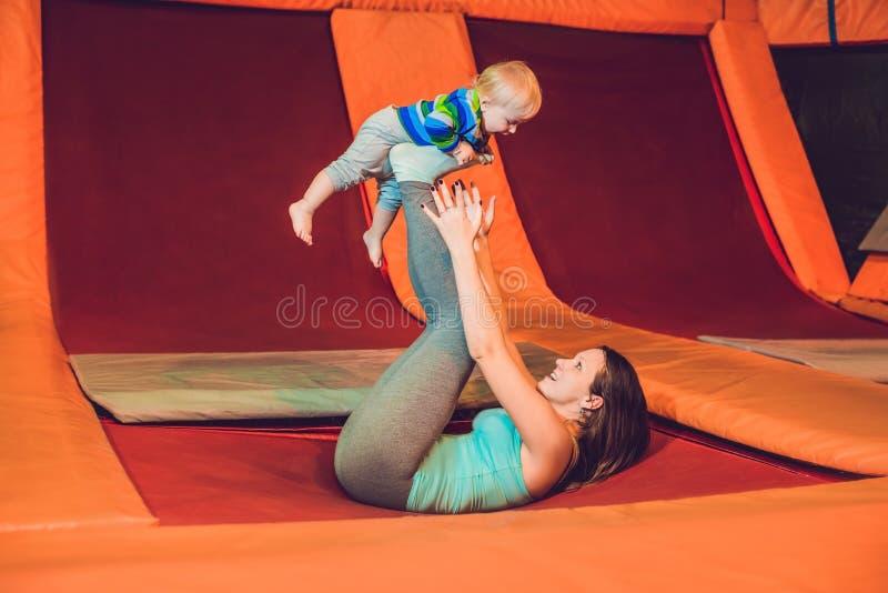 Modern och hennes sonbanhoppning på en trampolin i kondition parkerar och D royaltyfria foton