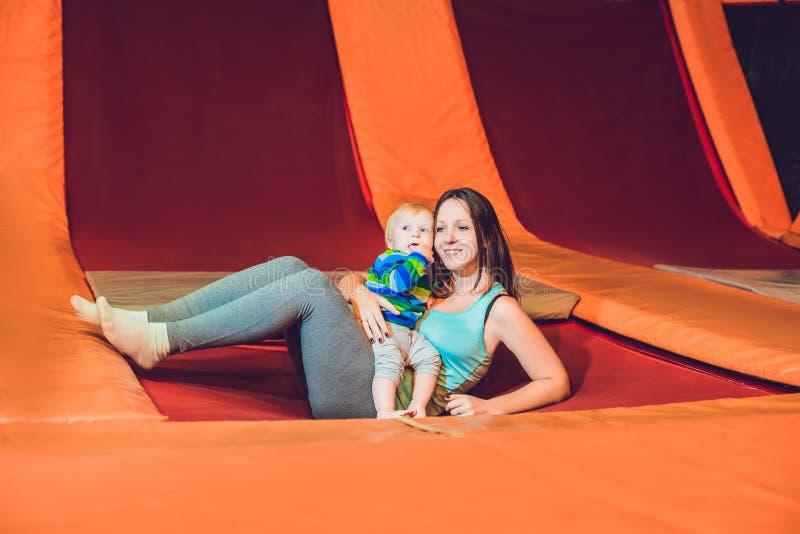 Modern och hennes sonbanhoppning på en trampolin i kondition parkerar och D royaltyfri fotografi
