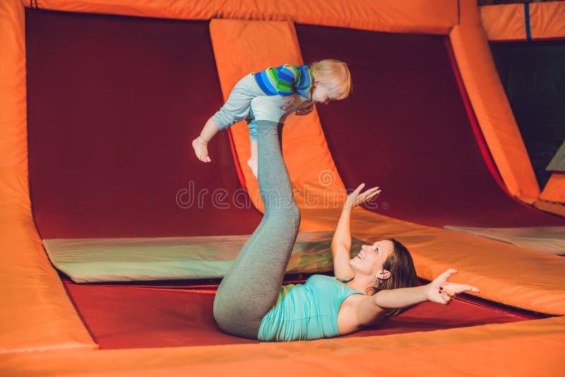 Modern och hennes sonbanhoppning på en trampolin i kondition parkerar och göra exersice inomhus royaltyfri fotografi