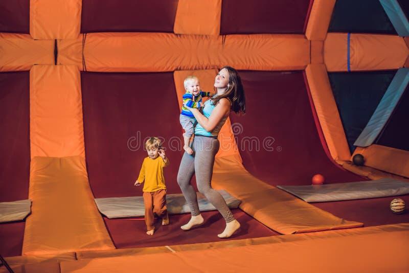 Modern och hennes sonbanhoppning på en trampolin i kondition parkerar och göra exersice inomhus arkivbild
