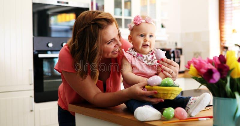 Modern och hon behandla som ett barn måla easter ägg arkivfoto