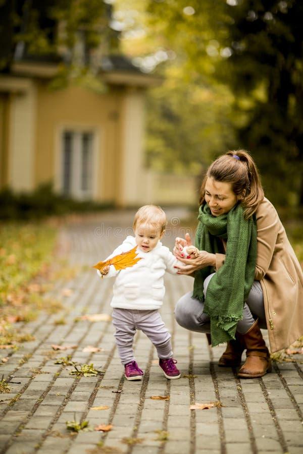 Modern och lilla flickan i hösten parkerar arkivfoto