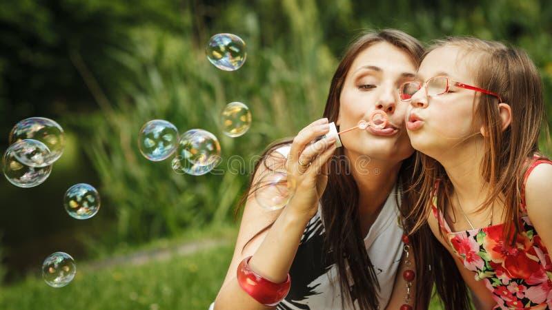 Modern och lilla flickan som blåser såpbubblor parkerar in royaltyfri foto