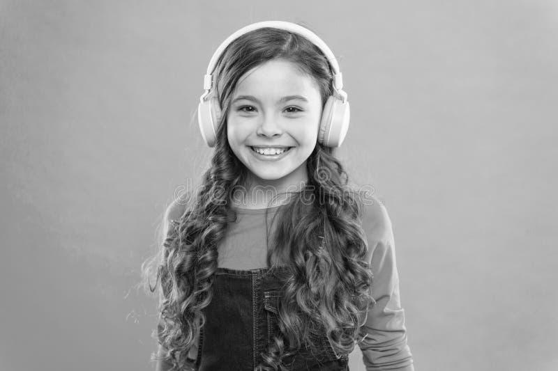 Modern och snygg Glad liten flicka som njuter av modern musik i blå bakgrund Liten flicka i snygga hörlurar royaltyfri bild