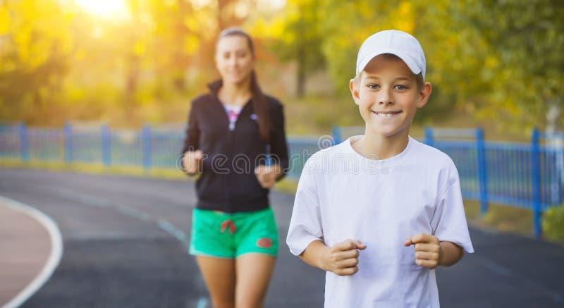 Modern och sonen är köra eller jogga för sport utomhus arkivbild
