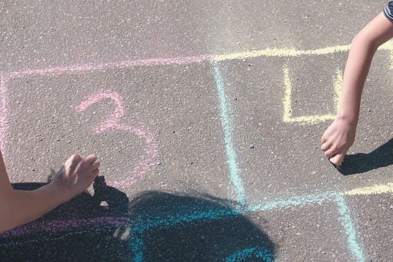 Modern och sonen drar nummer två och tre på hoppa hage på asfalt royaltyfria bilder