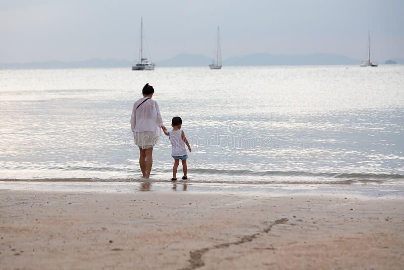 Modern och sonen går på stranden och blicken på vattnet och yachterna i havet arkivbild