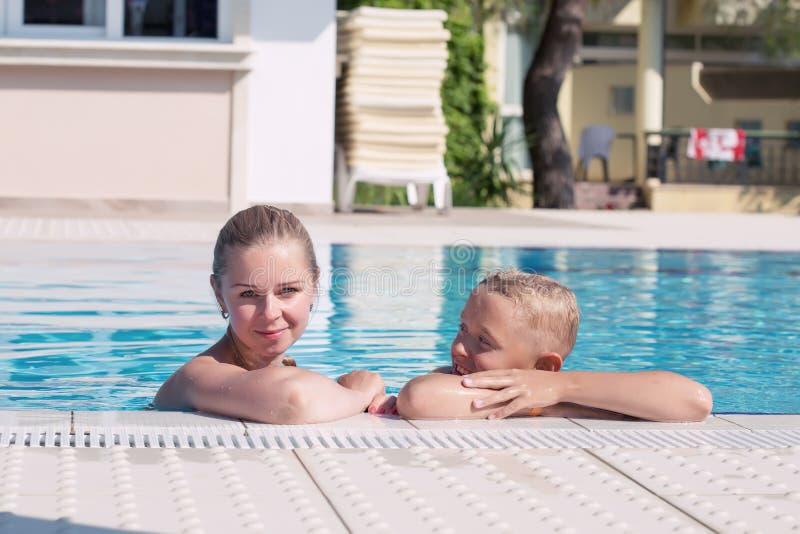 Modern och sonen har gyckel av en simbassäng arkivfoto