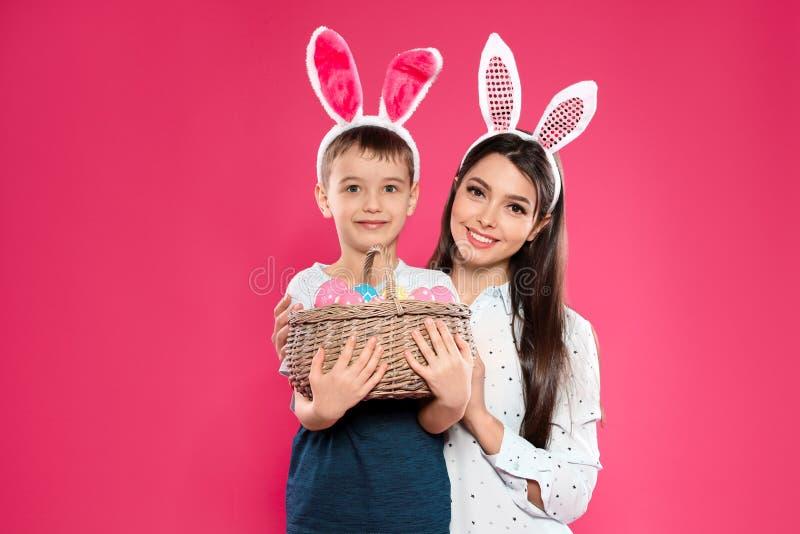 Modern och sonen i kanin gå i ax huvudbindlar med korgen av påskägg arkivbild