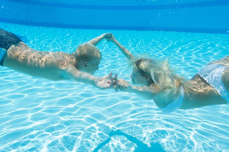 Modern och sonen simmar undervattens- arkivbilder