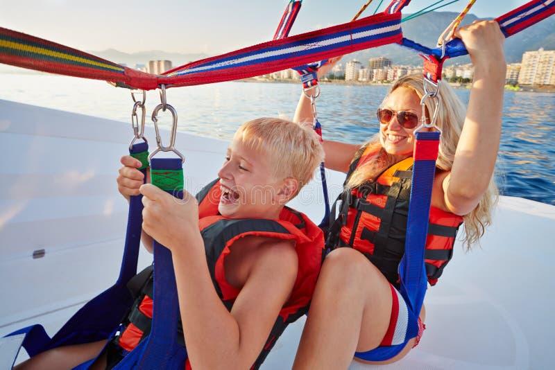 Modern och sonen sitter i motorbåt och ordnar till till paragliden royaltyfri bild