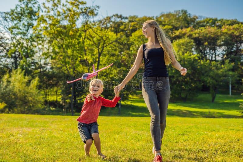 Modern och sonen som spelar med ett leksakflygplan för stor modell i, parkerar royaltyfri foto