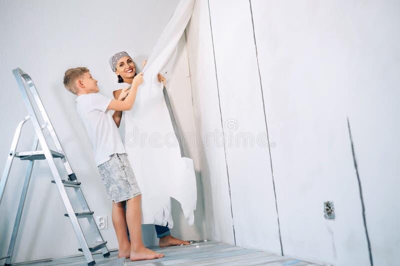Modern och sonen tar av tapeter från väggen och förbereder rum fo royaltyfri fotografi