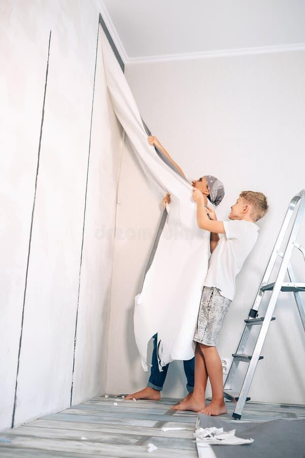 Modern och sonen tar av tapeter tillsammans arkivbilder
