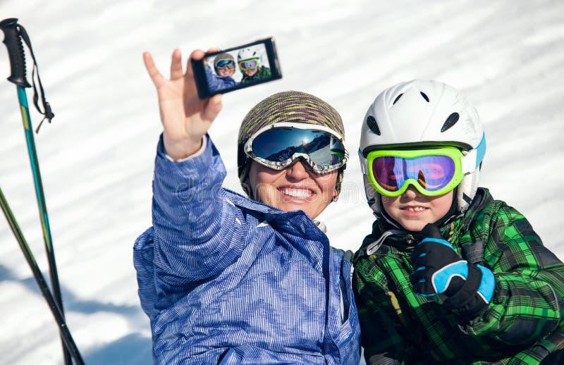 Modern och sonen tar ett selfiefoto på snökullen royaltyfri fotografi