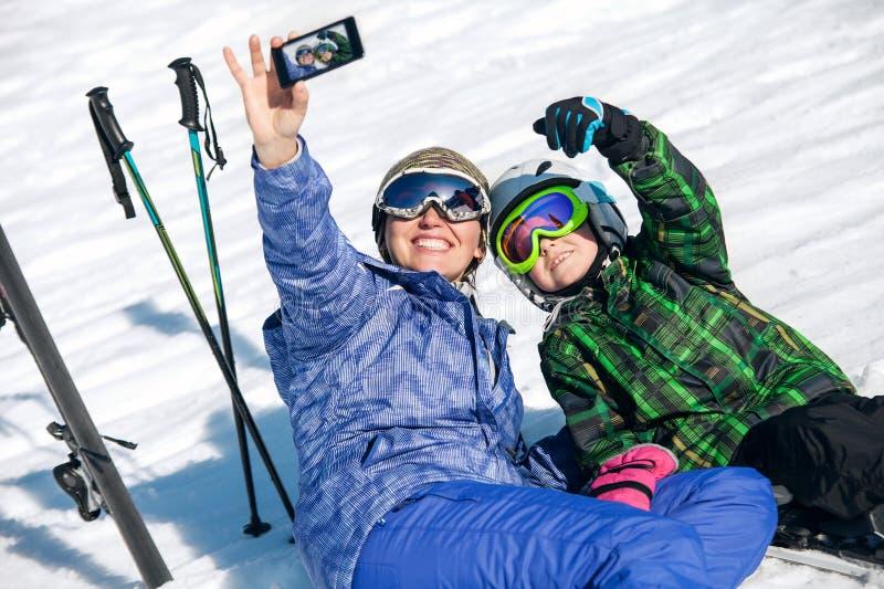 Modern och sonen tar ett selfiefoto skidar på semesterorten arkivfoton