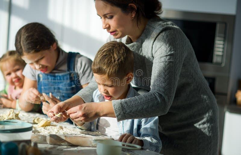 Modern och tre barn förbereder något från degen arkivfoton