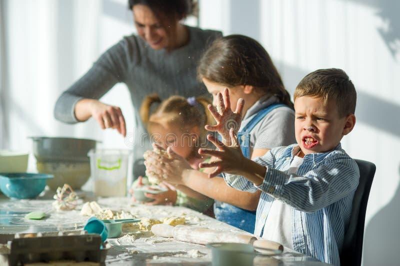 Modern och tre barn förbereder något från degen royaltyfri bild