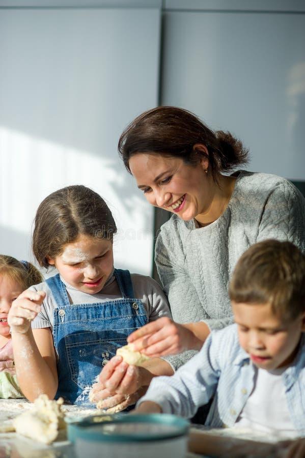 Modern och tre barn förbereder något från degen royaltyfri foto
