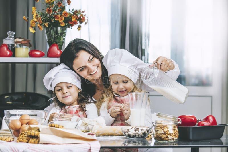 Modern och två lyckliga små behandla som ett barn flickan som att dricka mjölkar, och lagar mat på arkivfoto