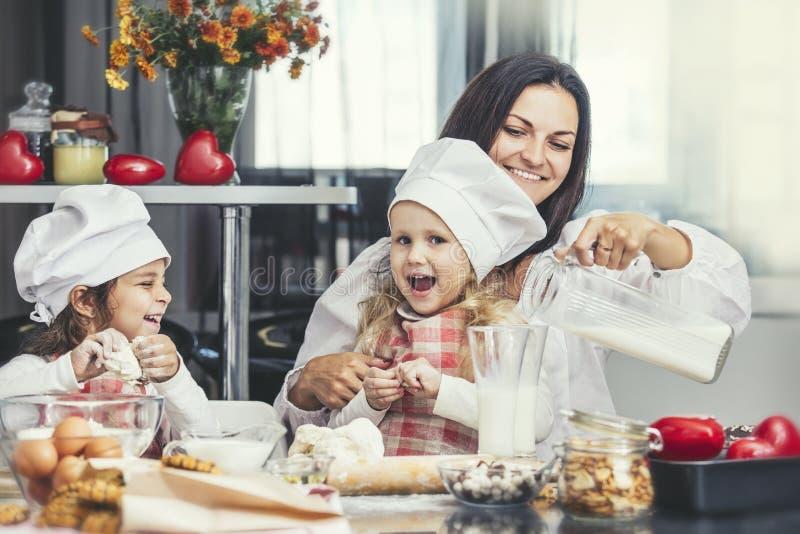 Modern och två lyckliga små behandla som ett barn flickan som att dricka mjölkar, och lagar mat på royaltyfri bild