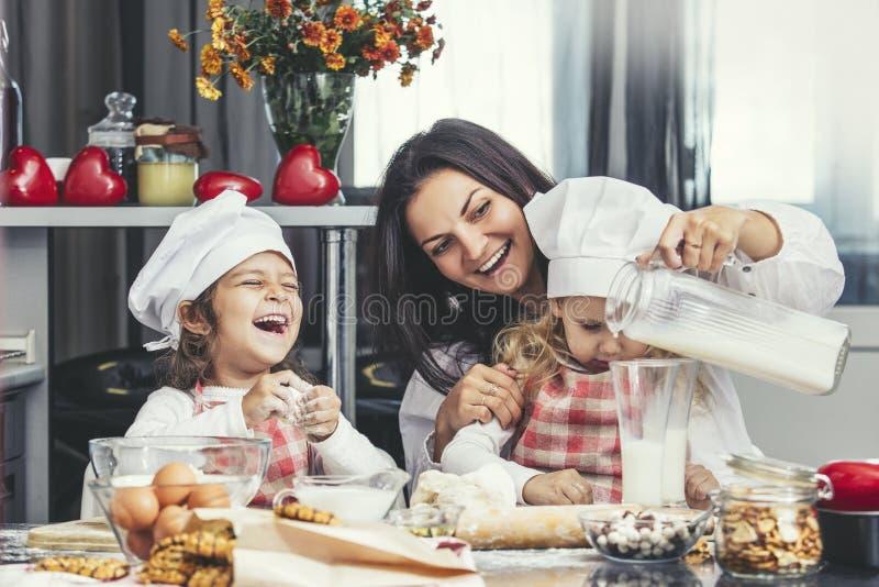 Modern och två lyckliga små behandla som ett barn flickan som att dricka mjölkar, och lagar mat på royaltyfria foton