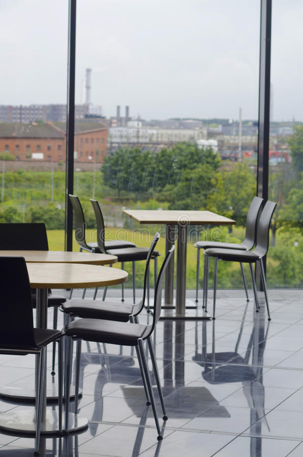 Modern office building cafeteria seating area. Cafeteria seating area with tables and chairs in a modern office building with glass windows. Outside overlooking stock image