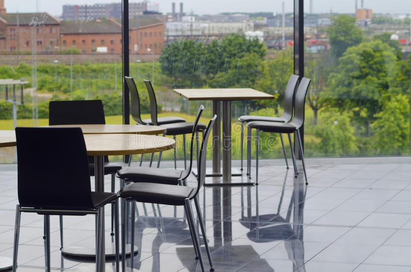 Modern office building cafeteria seating area. Cafeteria seating area with tables and chairs in a modern office building with glass windows. Outside overlooking stock photography