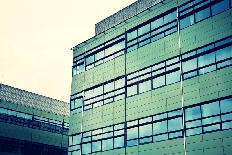Modern office building on a clear sky background. Retro stylized colorful tonal filter effect. Modern office building facade abstract fragment, shiny windows in stock photography