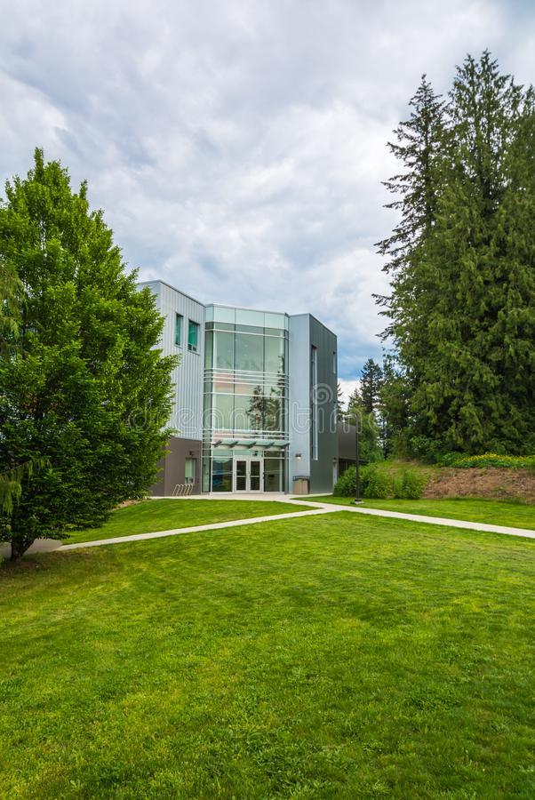 Modern office building with concrete pathways in front and trees around stock photo