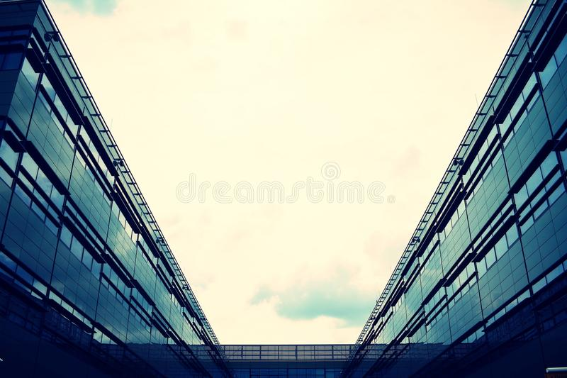 Modern office building on a clear sky background. Retro stylized colorful tonal filter effect. Modern office building facade abstract fragment, shiny windows in royalty free stock image