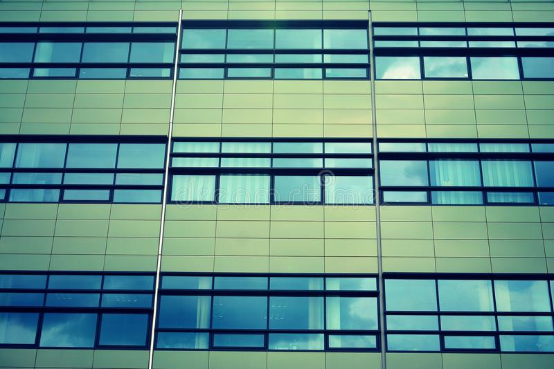 Modern office building on a clear sky background. Retro stylized colorful tonal filter effect. Modern office building facade abstract fragment, shiny windows in royalty free stock images