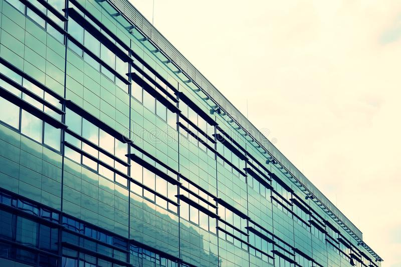 Modern office building on a clear sky background. Retro stylized colorful tonal filter effect. Modern office building facade abstract fragment, shiny windows in stock images