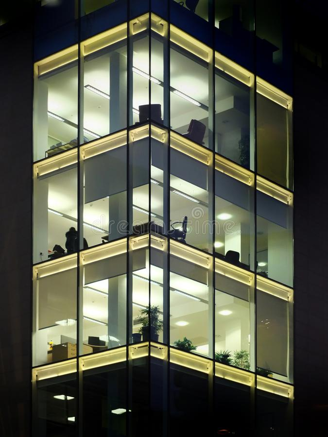 modern office building illuminated at night with geometric windows royalty free stock photography