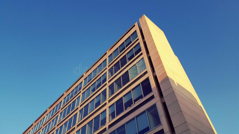 Modern office building. Low angle view showing the corner of a modern office building, blue sky background stock photos