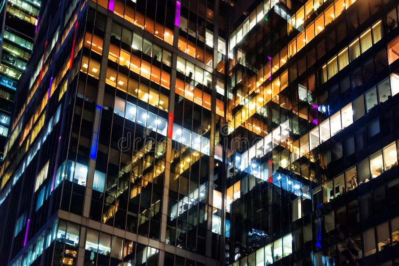Modern office building made from glass at night time. Lights in the office windows. stock photo