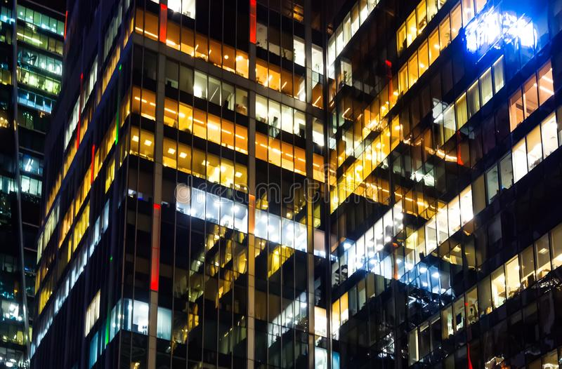 Modern office building made from glass at night time. Lights in the office windows. stock image