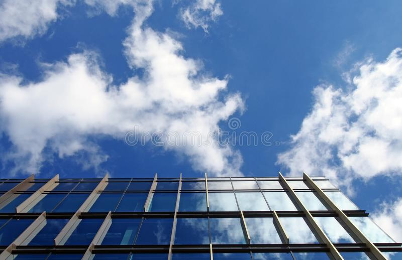Modern office building with mirrored glass windows reflecting a bright blue sky and white clouds. A modern office building with mirrored glass windows reflecting royalty free stock photos