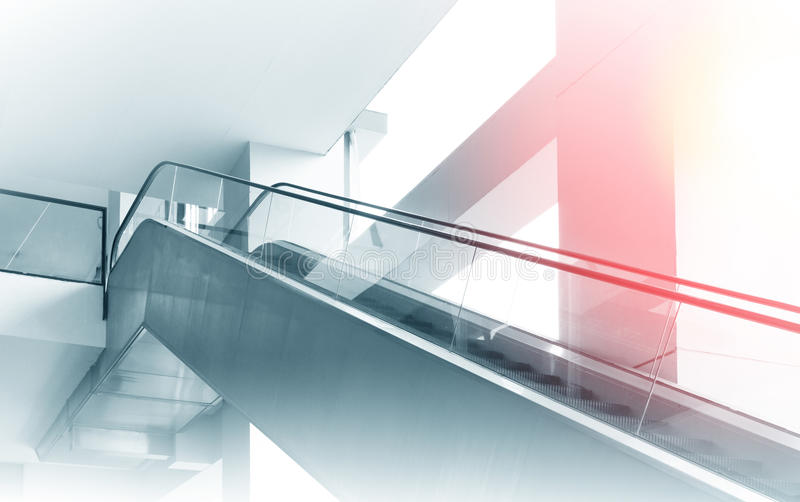 Modern office building and moving escalator stairs stock photography