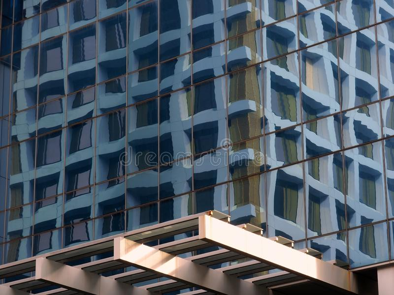Modern Office Building Reflected in Glass Windows. Detail of a modern high ruse commercial office building reflected in the glazed facade of an opposite building stock photography