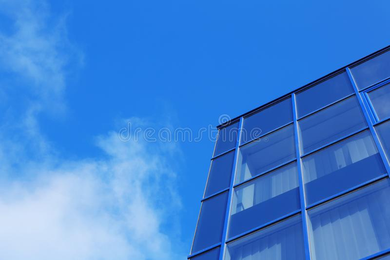 Modern office building with tinted windows against sky stock image