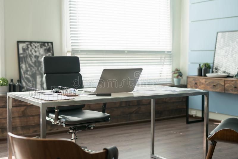 Modern office interior design with office chair and desk in front of windows. Workplace royalty free stock photos