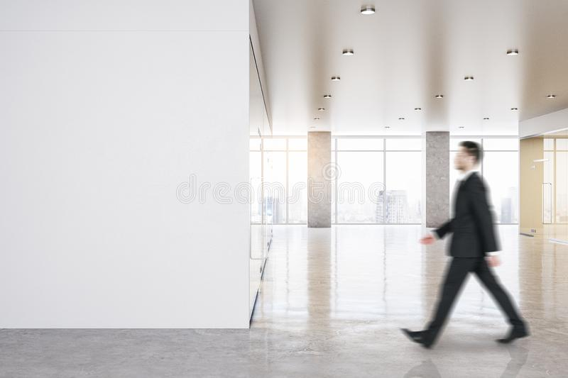 Modern office interior with poster. Side view of businessman walking in modern office interior with empty poster, city view and daylight. Mock up stock photography