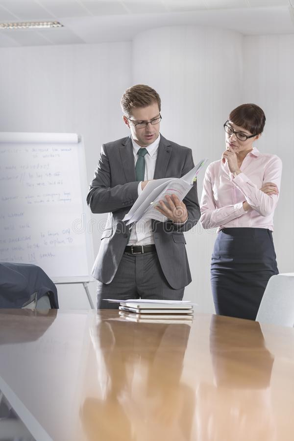Mid adult business colleagues discussing over documents in boardroom at office during meeting royalty free stock photo