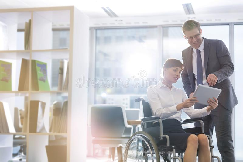 Smiling disabled businesswoman discussing over digital tablet with businessman at office royalty free stock photography