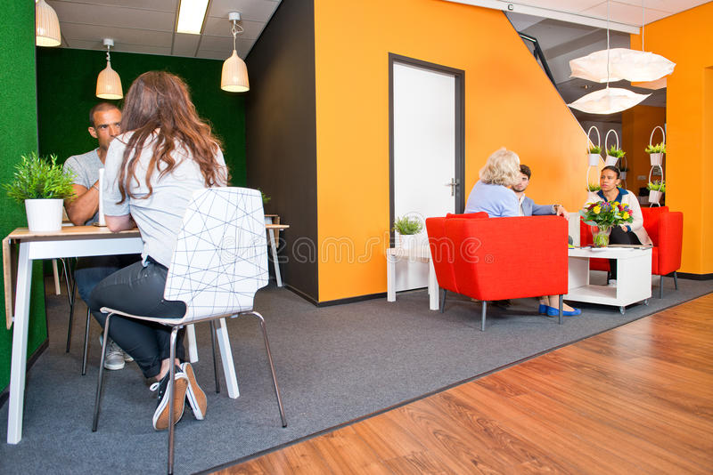 Modern office waiting area. Lobby and multi-purpose waiting area, with several groups of people sitting at tables during informal meetings of a modern styled royalty free stock photos
