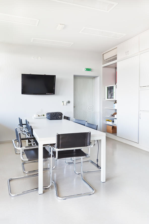 Modern office with white furniture. Cupboard, conference desk and walls and with plasma TV on the wall royalty free stock photo